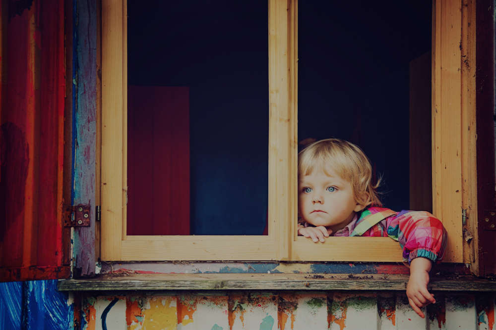 Small Blonde Child Gazing Out of a Window